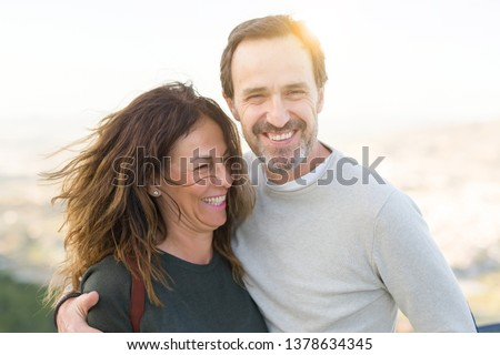 Romantic couple smiling and cuddling on a sunny day