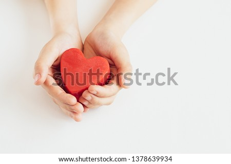 Child's hands holding red heart on white background with copy space. Mother's Day background. International Heart Day  concept. #1378639934