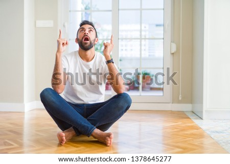 Handsome hispanic man wearing casual t-shirt sitting on the floor at home amazed and surprised looking up and pointing with fingers and raised arms. #1378645277