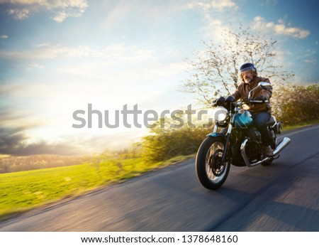 Motorcycle driver riding in European road. Outdoor photography, countryside landscape. Travel and sport photography. Speed and freedom concept #1378648160