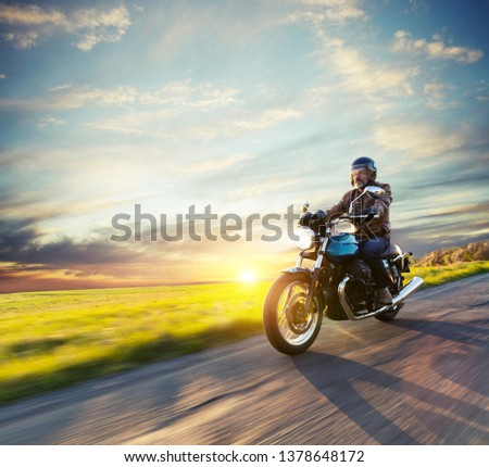Motorcycle driver riding in European road. Outdoor photography, countryside landscape. Travel and sport photography. Speed and freedom concept #1378648172