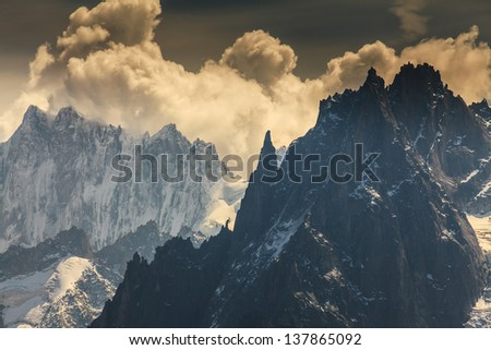Snow covered peaks and rocky cliffs in the Alps in summer