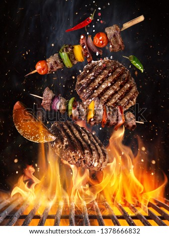 Tasty beef steaks and skewers flying above cast iron grate with fire flames. Freeze motion barbecue concept. #1378666832