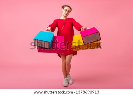 attractive happy smiling stylish woman shopaholic in red trendy dress holding colorful shopping bags on pink studio background isolated, sale excited, spring summer fashion trend #1378690913