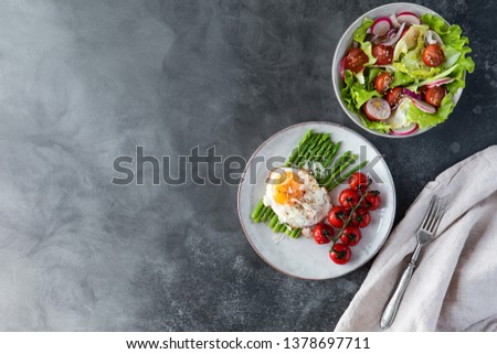 Blanched asparagus, fried egg, tomatoes and sald on the bowl, top view. Breakfast concept #1378697711