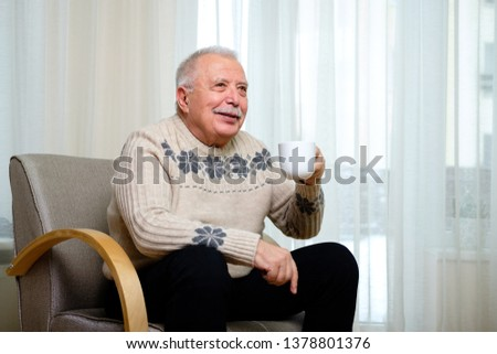 Portrait of happy and smiling senior male 70-75 years old sitting at home on the armchair, holding cup of coffee in hand on window background and looking to direct #1378801376
