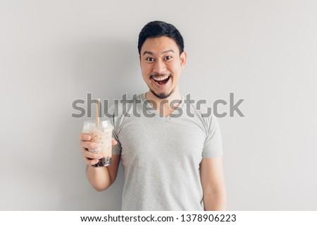 Happy Asian man is drinking Bubble Milk Tea or Pearl Milk Tea. Popular Milk Tea in Asia and Taiwan. #1378906223