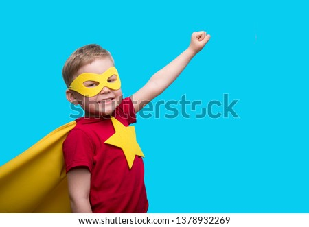 Little child superhero with yellow cloak and star. Happy smiling kid in glasses ready for education. Success, motivation concept. Back to school. Little businessman isolated on blue, Boy superhero.  #1378932269
