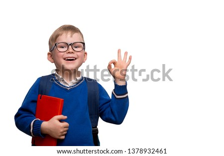 Back to school. Little boy in glasses with bag and book shows OK or alright sign. Success and happy kid isolated on white. Child from elementary school with book. Education. #1378932461