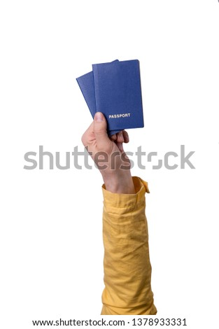 Hand hold blue passport isolated on gray background. hand in yellow  clothes. Vacation and summer holiday concept. #1378933331