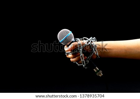 World press freedom day concept. Woman hand with microphone tied with a chain, depicting the idea of freedom of the press or freedom of expression on dark background. #1378935704