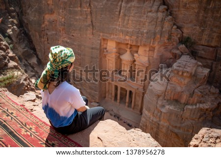 Asian woman traveler sitting on carpet viewpoint in Petra ancient city looking at the Treasury or Al-khazneh, famous travel destination of Jordan and one of seven wonders. UNESCO World Heritage site. #1378956278