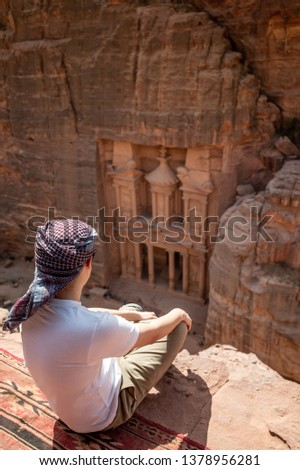 Asian man traveler sitting on carpet viewpoint in Petra ancient city looking at the Treasury or Al-khazneh, famous travel destination of Jordan and one of seven wonders. UNESCO World Heritage site. #1378956281