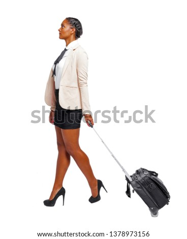 Side view of black African-American in formal attire walking with a suitcase. business woman in motion.  backside view of person.  Rear view people collection. Isolated over white background. B #1378973156