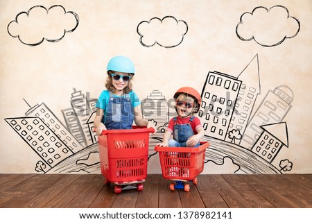 Happy children playing at home. Funny kids driving toy car indoor. Success and win concept #1378982141