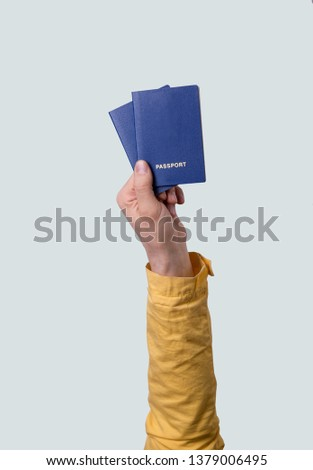 Hand hold blue passport isolated on gray background. hand in yellow  clothes. Vacation and summer holiday concept. #1379006495