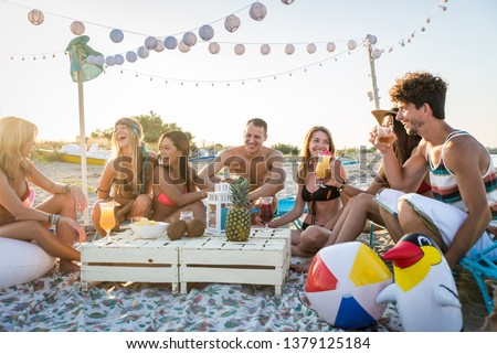 Group of friends having a picnic at the beach - Happy young people on a summer vacation at the beach