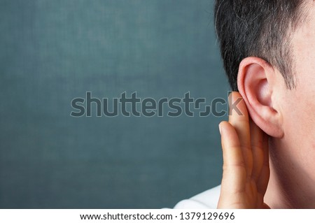 The man listens attentively with her palm to her ear, close up, the news concept Royalty-Free Stock Photo #1379129696
