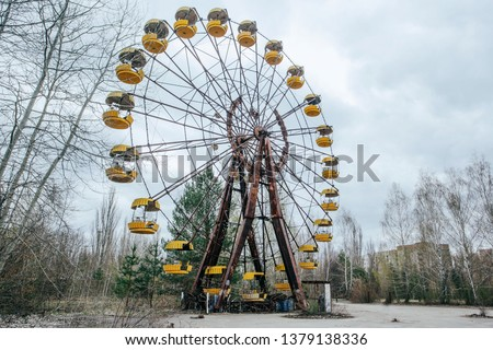 Abandoned carousel and abandoned ferris at an amusement park in the center of the city of Pripyat, the Chernobyl disaster, the exclusion zone, a ghost town #1379138336