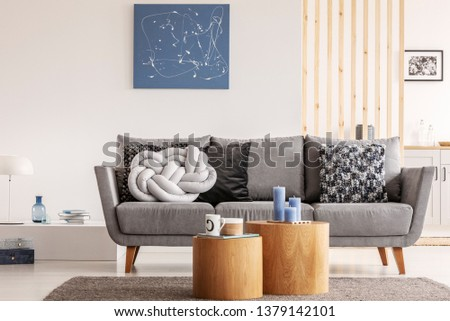 Blue abstract painting on white wall of contemporary living room interior with grey settee with pillows #1379142101