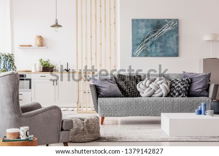 Open plan studio apartment with small white kitchen and living room with grey couch and wooden coffee table #1379142827