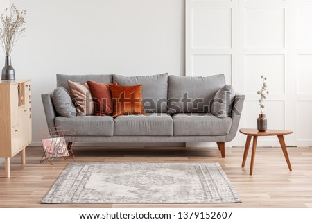Orange, red and beige pillows on grey comfortable couch in chic living room interior Royalty-Free Stock Photo #1379152607