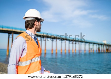 A young construction graduate engineer with a white helmet is looking at the construction of the jetty on the sea, from the coast. #1379165372