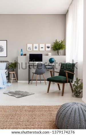 Grey pouf on natural linen carpet in fashionable teenager's room with retro armchair and industrial desk with computer #1379174276