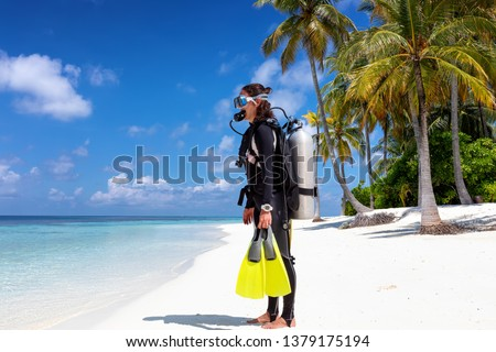 Female scuba diver in full equipment stands on a tropical beach ready to enter the water Royalty-Free Stock Photo #1379175194
