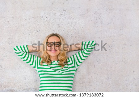 young, pretty blonde woman posing in front of a concrete wall and wearing green, white striped sweaters #1379183072