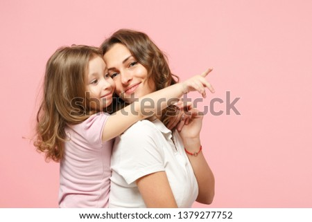 Woman in light clothes have fun with cute child baby girl. Mother, little kid daughter isolated on pastel pink wall background, studio portrait. Mother's Day love family, parenthood childhood concept #1379277752