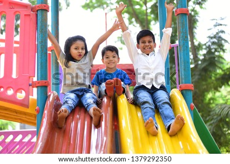 Kids having fun and sliding on outdoor playground. Kids Enjoying Royalty-Free Stock Photo #1379292350