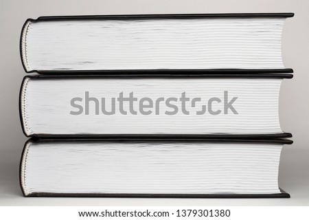An even stack of three untitled black hardcover books that lie one upon another. Collection of volumes isolated on white paper background. Pages and binding of a closed book close up. Bottom side view #1379301380