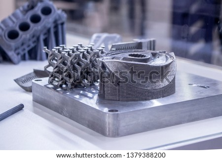 Man is holding object printed on metal 3d printer. Object printed in laser sintering machine. Modern 3D printer printing from metal powder. Progressive additive DMLS, SLM, SLS 3d printing technology #1379388200