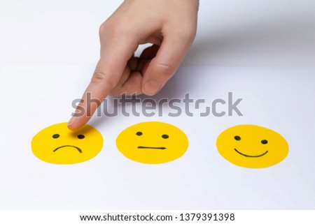 Cut out of paper mood emoticons on a white background. The finger of the hand indicates the chosen mood. #1379391398