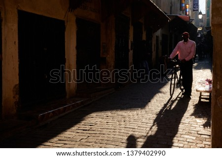 Fez, Morocco - December 07 2018: Moroccan gentleman walking down an old street in the medina of fez with a bicycle #1379402990