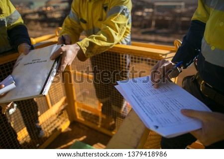 Trained miner supervisor checking reviewing document issued sign approvals of working at height permit JSA risk assessment on site prior to performing high risk work construction mine site, Australia  #1379418986