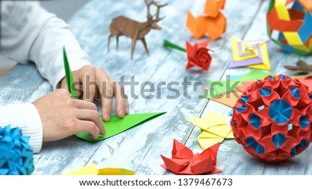 Man at origami folding lesson. Collection of beautiful origami figurines on wooden table. Traditional origami paper folding. #1379467673