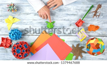Man at origami folding lesson. Man pointing at origami frog with finger. Collection of beautiful origami figurines on wooden table. Traditional origami paper folding. #1379467688