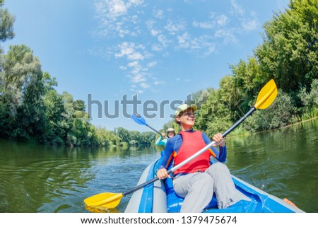 Happy family kayaking on the river. Active girl with her mother having fun enjoying adventurous experience with kayak on a sunny day during summer vacation #1379475674