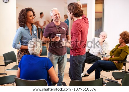Group Of People Socializing After Meeting In Community Center Royalty-Free Stock Photo #1379510576