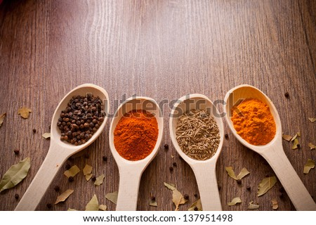 aromatic powder spices on spoons in wooden background #137951498