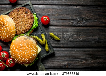 Burgers with tomatoes on a branch and gherkins. On black wooden background #1379533316