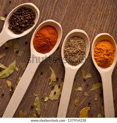 aromatic powder spices on spoons in wooden background #137954228