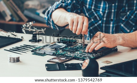 Computer repair shop. Engineer performing laptop maintenance. Hardware developer fixing electronic components. PC technology #1379542769