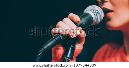Singer at microphone. Woman singing and holding mic. Female vocal talent. Music show recital. #1379544389