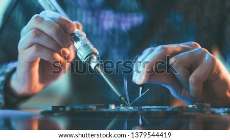 Electronic renovation in repair shop. Engineer working on circuit. Closeup of male hands soldering computer component. #1379544419