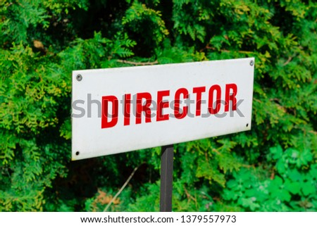 Director parking sign, red letters, reserved place, behind green natural background. Sunny daylight. #1379557973