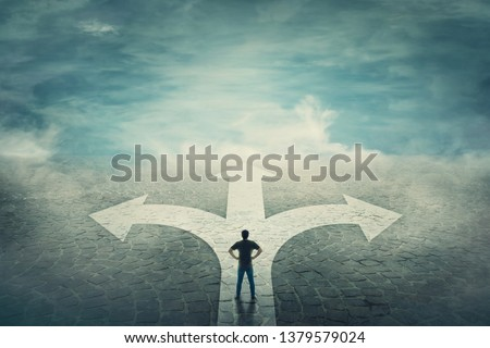 Confident man, hands on hips, stands in front of a crossroad with road split in three different ways as arrows. Choosing the correct pathway between left, right and front. Difficult decision concept. Royalty-Free Stock Photo #1379579024