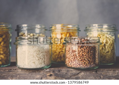Various raw cereals, grains, beans and pasta for cooking healthy food in glass jars on a wooden table, on a gray background,  Clean food, vegan, balanced diet,zero waste,eco friendly,plastic free #1379586749